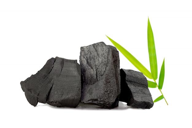Natuurlijke houtskool, bamboe houtskool poeder heeft geneeskrachtige eigenschappen met traditionele houtskool geïsoleerd op een witte achtergrond