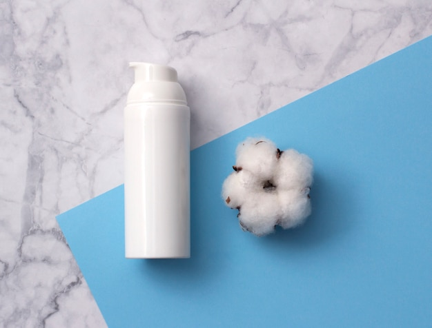 Natuurlijke huidverzorging cosmetisch product met katoen bloem op wit marmeren tafel van bovenaf.