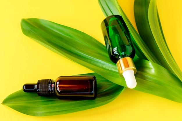 Natuurlijke huidverzorging fles container en biologisch groen blad op gele achtergrond. zelfgemaakte remedie en schoonheidsproduct concept.