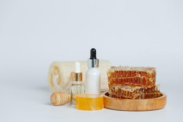 Natuurlijke huidverzorging zeep en serum met honing en honingraat gelegd op wit oppervlak.