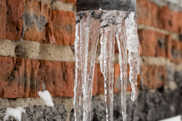 Natuurlijke ijspegels die op de pijp hangen