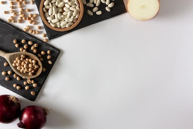 Natuurlijke ingrediënten. kikkererwten op leisteendienblad en uien. plat leggen. ruimte kopiëren.