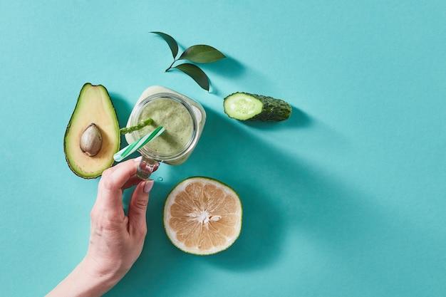 Natuurlijke ingrediënten voor een gezonde smoothie van avocado met komkommer, selderij, shpinazie, citroen in pot op groen. concept van veganistisch en gezond eten.