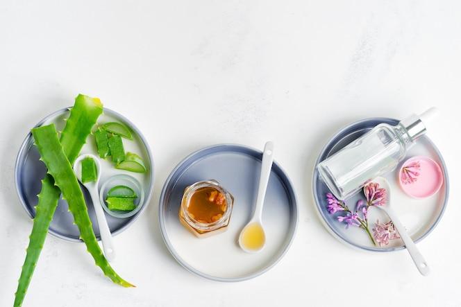 Natuurlijke ingrediënten voor het maken van cosmetische zelfgemaakte lotion of etherische olie op lichtgrijs.