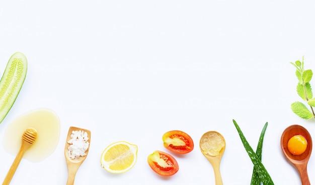 Natuurlijke ingrediënten voor zelfgemaakte huidverzorging op witte achtergrond.
