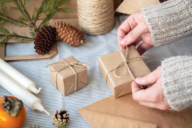 Natuurlijke kerstachtergrond, ambachtelijke geschenkdozen, kegels, kerstboom op tafel, close-up, retro-stijl. een meisje in een trui is cadeautjes aan het inpakken. de vrolijke sfeer van de vakantie.