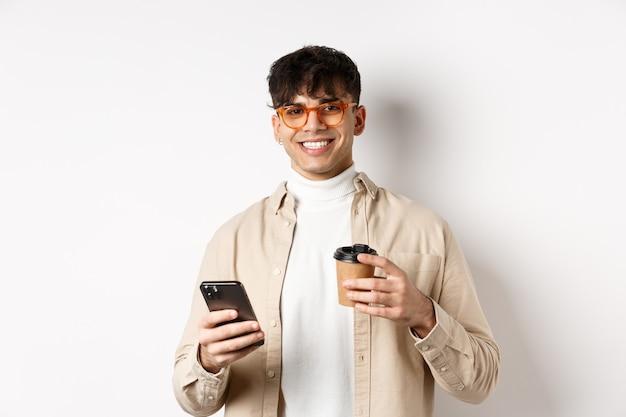 Natuurlijke knappe man in glazen die koffie drinkt uit een papieren beker en mobiele telefoon gebruikt, tevreden glimlachend in de camera, witte achtergrond.