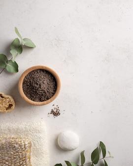 Natuurlijke koffiescrub in een houten kom en een badhanddoek op een witte stenen achtergrond met eucalyptustakken dagelijks bodycare-concept, biologische badproducten plat leggen, kopie ruimte,