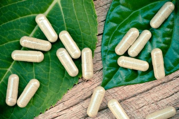 Natuurlijke kruidcapsules op groen blad en rustieke lijst