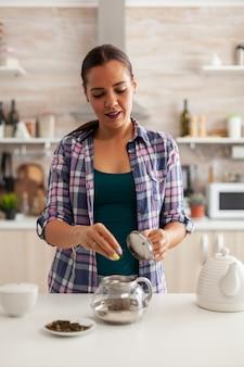 Natuurlijke kruiden gebruiken in de keuken om thee te bereiden tijdens het ontbijt