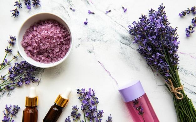 Natuurlijke kruidencosmetica met lavendel, flatlay op wit marmeren oppervlak, bovenaanzicht