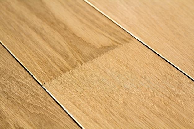 Natuurlijke lichtbruine houten parketvloerplanken. zonnige zachte gele textuur, kopie ruimte perspectief achtergrond.