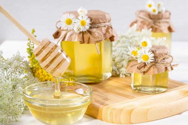 Natuurlijke lichte vloeibare honing. honing in glazen potten en beer op wit oppervlak met bloemen.