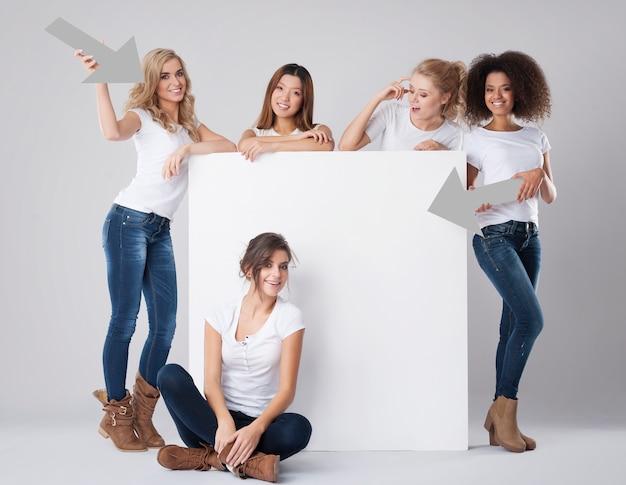 Natuurlijke meisjes met verschillende nationaliteiten die op wit bord tonen
