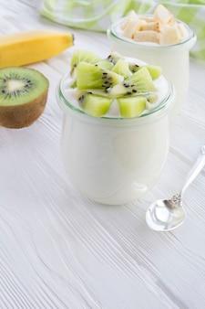 Natuurlijke melkyoghurt met kiwi en banaan in de glazen potten