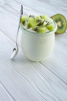 Natuurlijke melkyoghurt met kiwi in de glazen pot