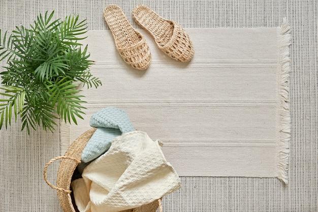 Natuurlijke mousseline handdoeken wit en zacht blauw liggen in een rieten mand tegen een wit katoenen kleed en