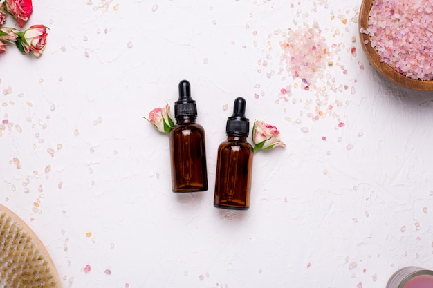 Natuurlijke olieflessen met bloemen en badzout op wit