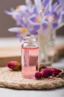Natuurlijke pure rozenolie of geparfumeerd water in flessen voor spa, huidverzorging of aromatherapie met roze rozen droog. biologische cosmetica concept. selectieve aandacht