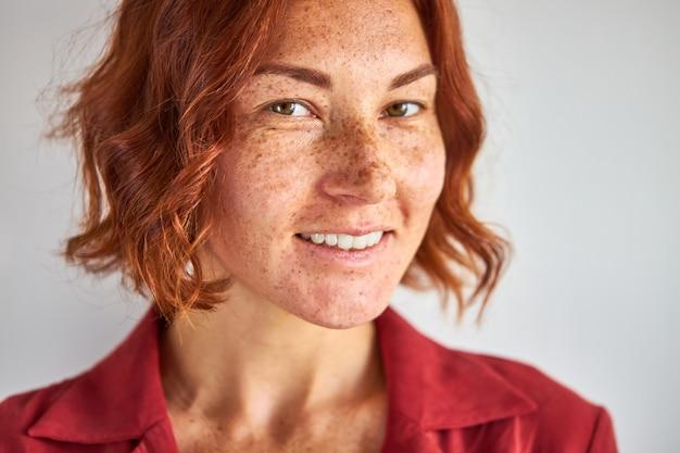 Natuurlijke roodharige vrouw met sproeten poseren op camera geïsoleerd in studio, natuurlijke schoonheid, mensen en lifestyle concept