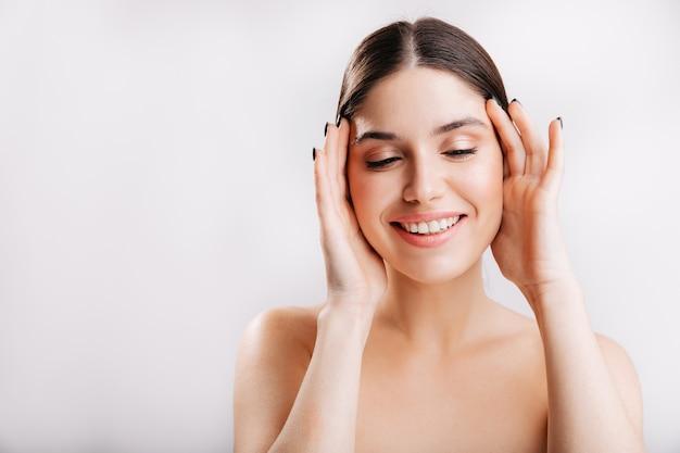 Natuurlijke schoonheid. jonge europese vrouw zonder make-up en filters die op geïsoleerde muur stellen.