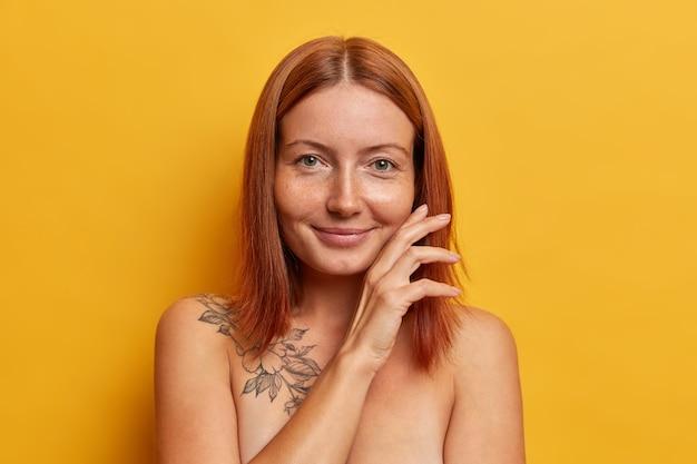 Natuurlijke schoonheid, zuiverheid en wellnessconcept. tevreden roodharige vrouw raakt gezicht zachtjes aan, demonstreert haar perfect gladde huid na spa-procedure, staat met blote schouders tegen gele muur
