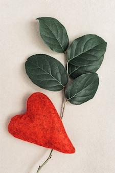 Natuurlijke tak met groene bladeren en rood hart.