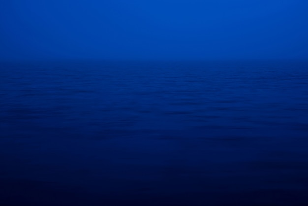 Natuurlijke textuur van diep blauw kalm water in schemer dichte omhooggaand. nacht zee van blauwe klassieke kleur. de aardachtergrond van de waterrimpeling. meditatieve beeld van dikke mist boven het meer. zacht licht schijnt op het wateroppervlak.