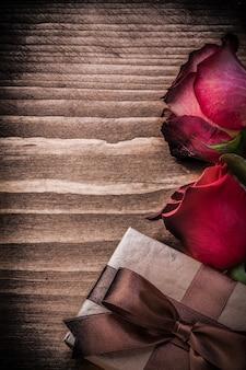Natuurlijke uitgebreide rozen huidige doos op houten bord vakantie concept