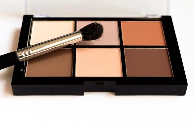 Natuurlijke uitstraling, bruine tint oogschaduwen vormen palet in zwarte behuizing.