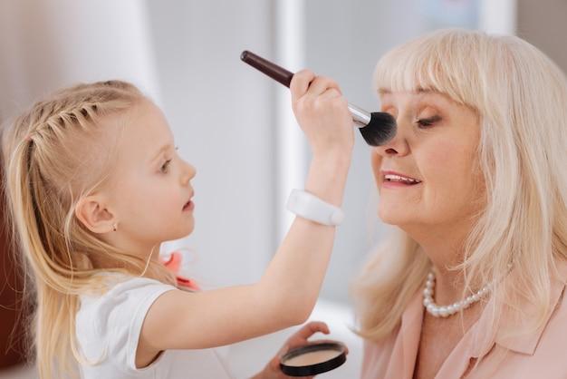 Natuurlijke uitstraling. leuk aardig mooi meisje dat een penseel vasthoudt en poeder op haar grootmoeders neus aanbrengt terwijl ze een natuurlijke look creëert