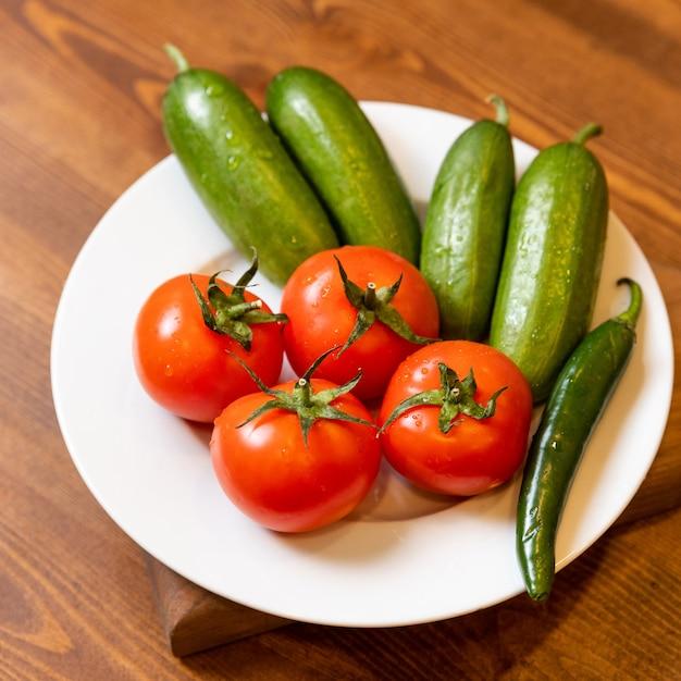 Natuurlijke verse tomaat, komkommer op de plaat