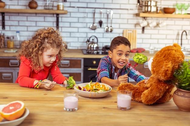 Natuurlijke vitamines. opgetogen jongen die glimlach op zijn gezicht houdt en broccoli op vork houdt