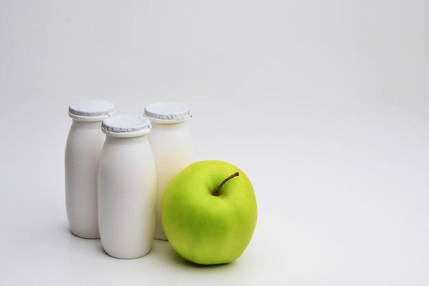 Natuurlijke vloeibare yoghurt met probiotica in kleine plastic fles en groene appel op witte achtergrond