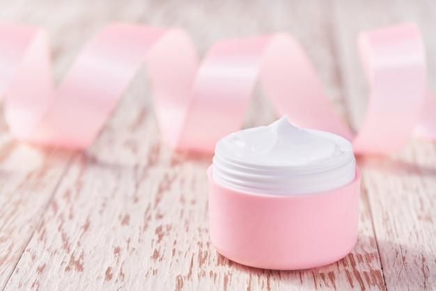 Natuurlijke vochtinbrengende crème of bodylotion cosmetische serie premium hydraterende en voedende cosmetica. plastic roze pot natuurlijke cosmetica op een houten tafel.