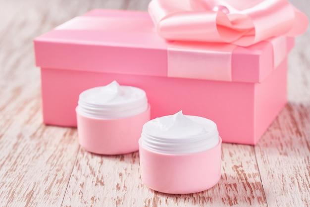 Natuurlijke vochtinbrengende crème of bodylotion cosmetische serie premium hydraterende en voedende cosmetica. plastic roze potten met natuurlijke cosmetica op een houten tafel.