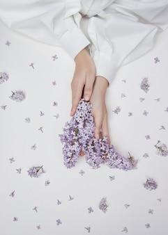 Natuurlijke vrouwcosmetica voor handen gemaakt van lila bloemen en bloemblaadjes. bevochtig en verzacht de huid van de handen. lila bloemen steken uit de mouwen van de arm