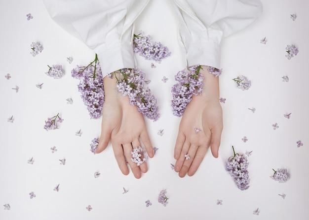 Natuurlijke vrouwcosmetica voor handen gemaakt van lila bloemen en bloemblaadjes.