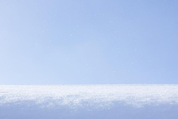 Natuurlijke winterachtergrond met sneeuwafwijkingen en vallende sneeuw