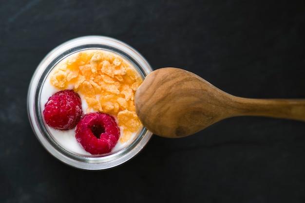 Natuurlijke yoghurt met aardbeienjam vergezeld van frambozen en ontbijtgranen
