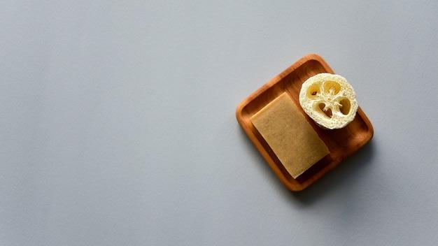 Natuurlijke zeep en loofah badspons op een houten plaat. grijs papier achtergrond. geen afvalconcept. bovenaanzicht.