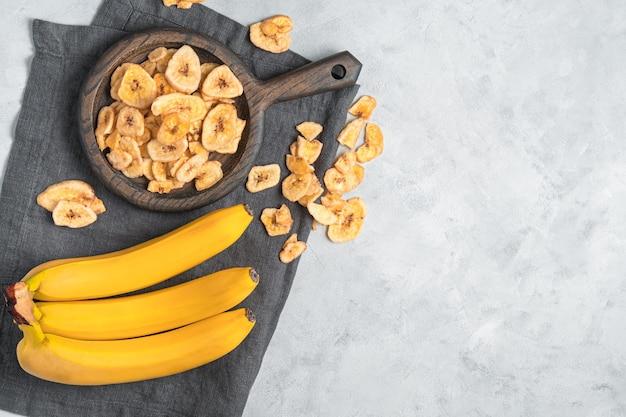 Natuurlijke, zelfgemaakte bananenchips en verse bananen op een grijze muur. bovenaanzicht, kopieer ruimte.