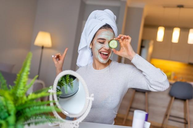 Natuurlijke zelfgemaakte gezichtsmaskers thuis. vrouw die masker op haar gezicht toepast en in de spiegel kijkt. mooie vrouw die natuurlijk gezichtsmasker toepast. schoonheidsbehandelingen.