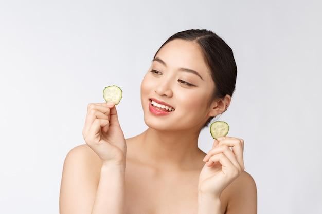 Natuurlijke zelfgemaakte verse komkommer gezichts eye pads gezichtsmaskers aziatische vrouw met komkommer pads en glimlach ontspannen met natuurlijke zelfgemaakte