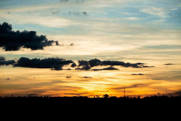 Natuurlijke zonsondergang zonsopgang boven veld of weide. heldere dramatische hemel en donkere grond.