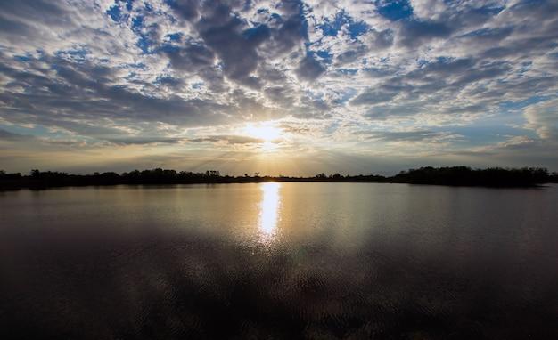 Natuurlijke zonsondergang zonsopgang. heldere dramatische lucht en donkere grond. platteland
