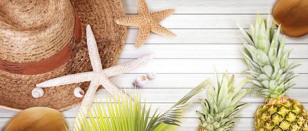 Nautisch concept met palmblad, strandhoed, zeester en ananas.
