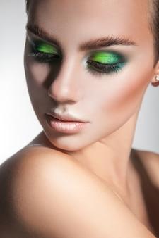 Nauwe portret van prachtig meisje met gesloten ogen en een prachtige make-up studio opname grijze achtergrond