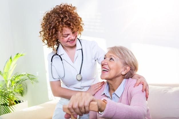 Nauwe positieve relatie tussen senior patiënt en verzorger. gelukkige hogere vrouw die aan een vriendschappelijke verzorger spreekt.