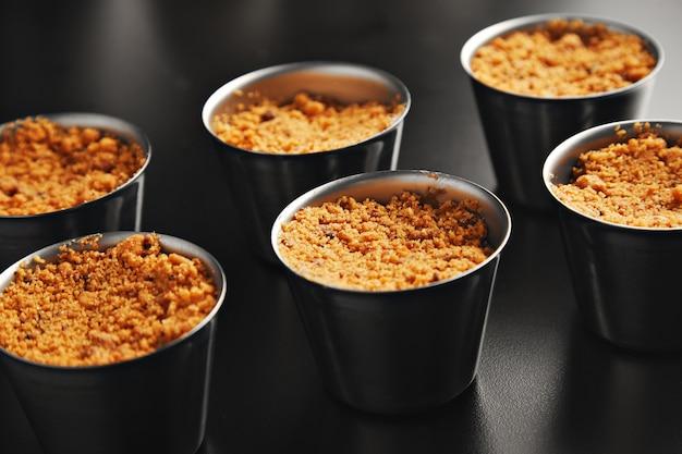 Nauwe weergave op zes porties appelkruimeldessert in afzonderlijke stalen bekers op glanzend zwarte tafel